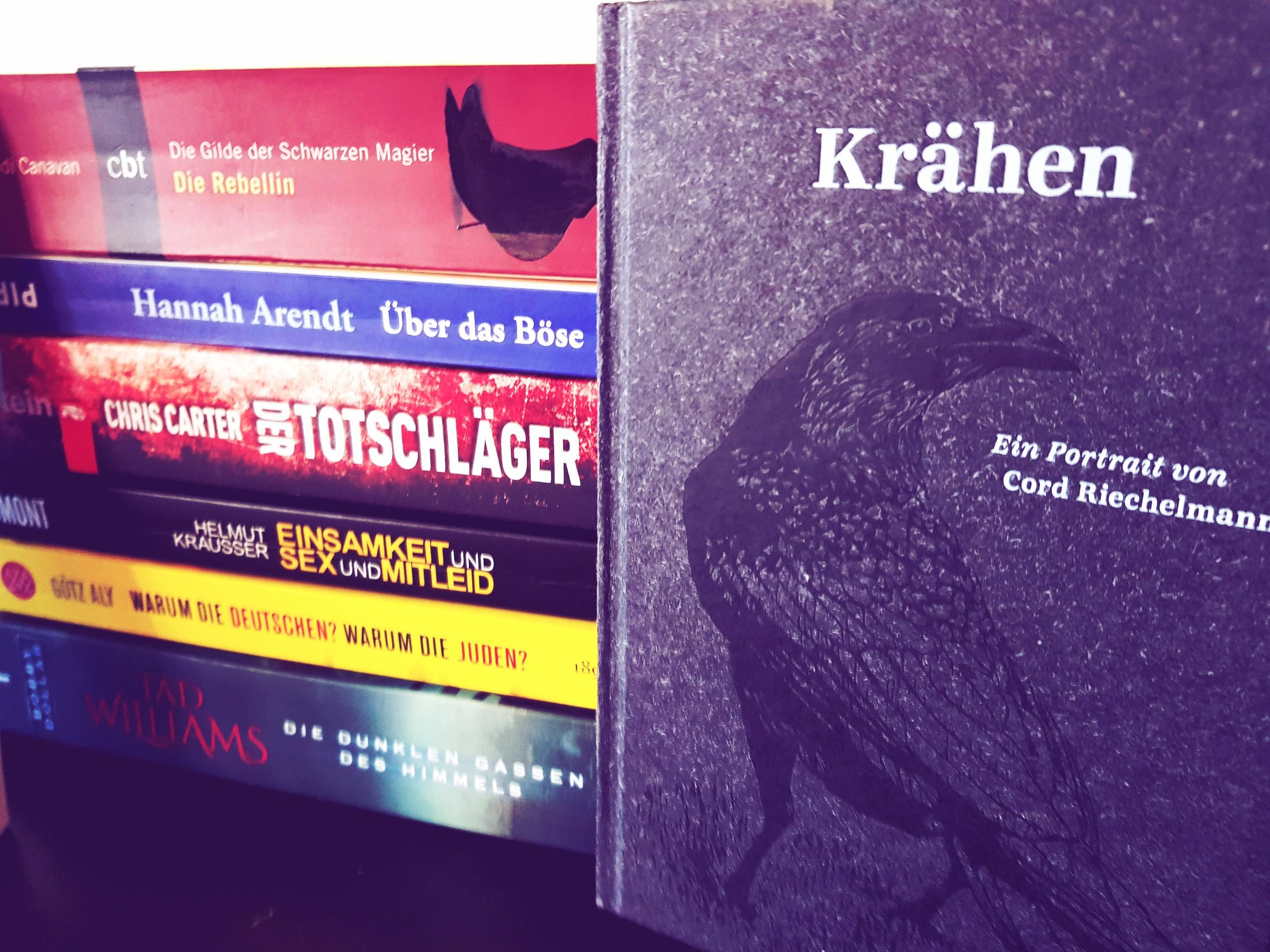 Buchstapel, im Vordergrund ein Buch über Krähen