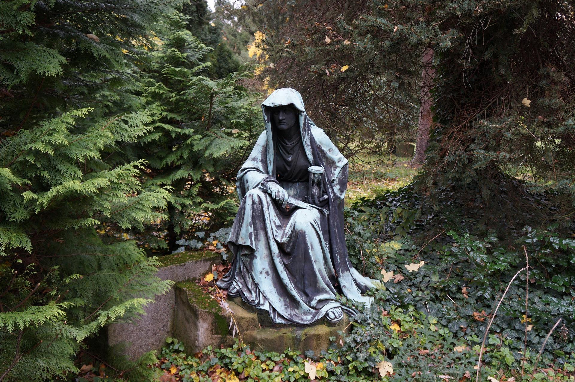 Kupferstatue mit Sanduhr im Wald
